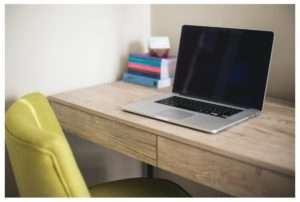laptop on brown table with yellow chair